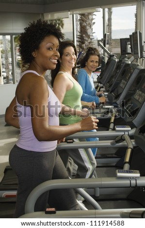 Multi ethnic women exercising on treadmill - stock photo