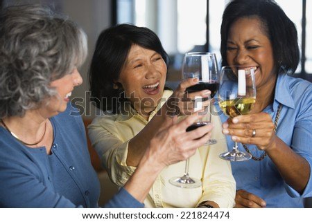 Multi-ethnic women toasting with wine - stock photo