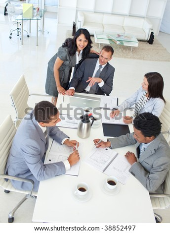 Multi-ethnic young business team working in a project in a meeting - stock photo