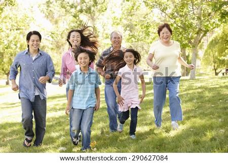 Multi-generation Asian family running in park - stock photo