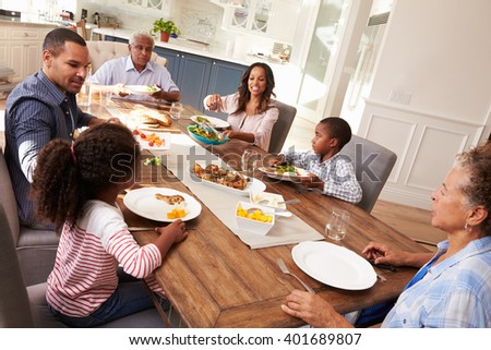 Multi generation black family serving a meal in the kitchen