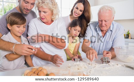 Multi-generation family baking together in the kitchen - stock photo