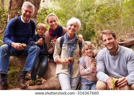 Multi-generation family eating in a forest, portrait - stock photo