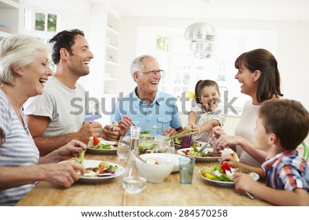 Multi Generation Family Eating Meal Around Kitchen Table - stock photo