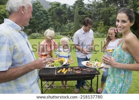 Multi-generation family enjoying barbecue and wine - stock photo