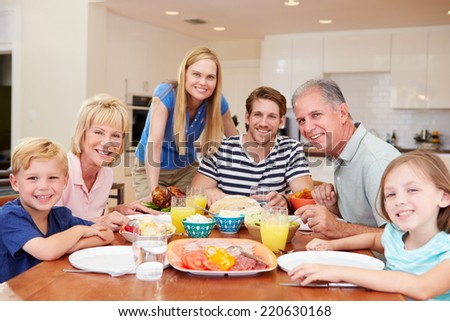 Multi Generation Family Enjoying Meal At Home Together