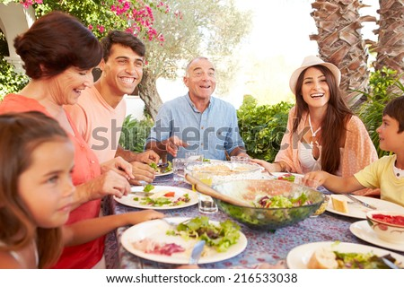 Multi Generation Family Enjoying Meal On Terrace Together - stock photo