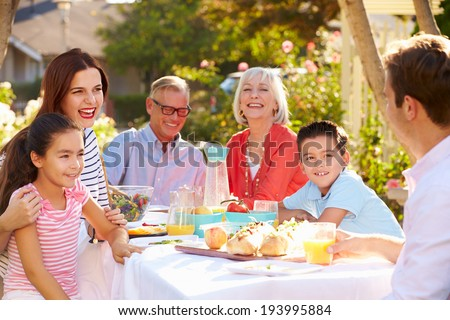 Multi-Generation Family Enjoying Outdoor Meal In Garden - stock photo