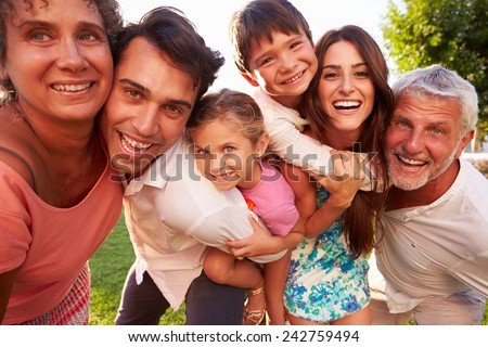 Multi Generation Family Giving Children Piggybacks In Park