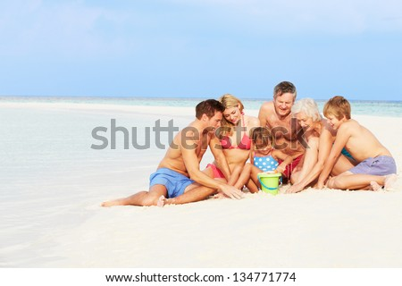 Multi Generation Family Having Fun On Beach Holiday - stock photo