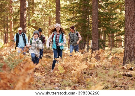 Multi generation family hiking in a forest, kids running - stock photo