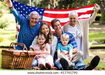 Multi-generation family holding american flag in the park on a sunny day - stock photo