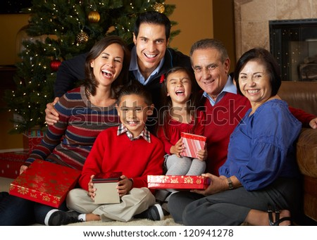Multi Generation Family In Front Of Christmas Tree - stock photo