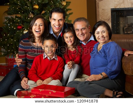 Multi Generation Family In Front Of Christmas Tree