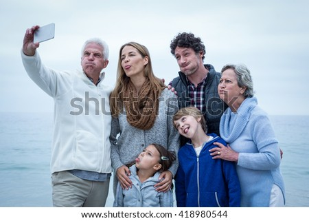 Multi-generation family making faces while taking selfie at sea shore - stock photo