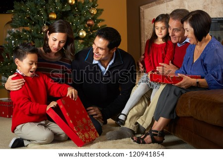 Multi Generation Family Opening Christmas Presents In Front Of Tree