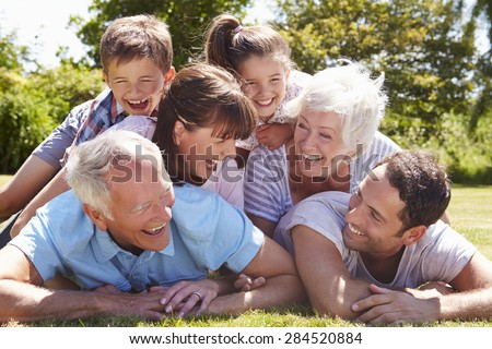Multi Generation Family Piled Up In Garden Together - stock photo