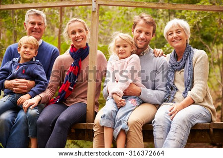 Multi-generation family portrait on a bridge in a forest - stock photo
