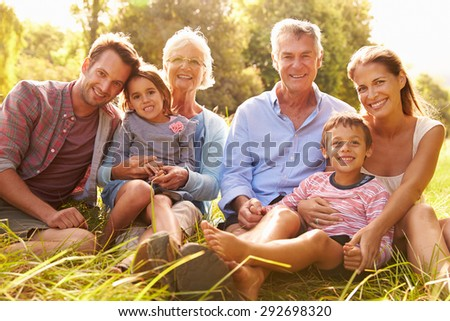 Multi-generation family relaxing together outdoors - stock photo