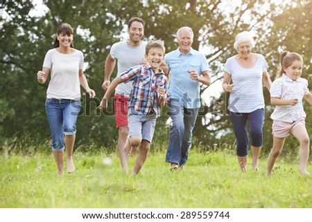 Multi Generation Family Running Across Field Together - stock photo