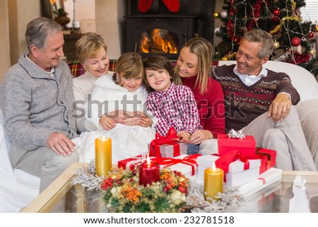 Multi generation family sitting on a couch during christmas at home in the living room - stock photo