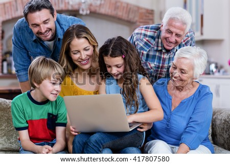 Multi-generation family sitting on sofa and using laptop at home - stock photo