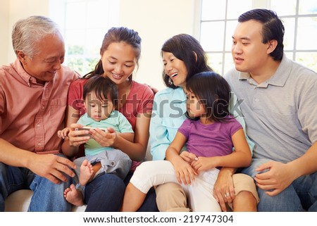 Multi Generation Family Sitting On Sofa With Mobile Phone - stock photo