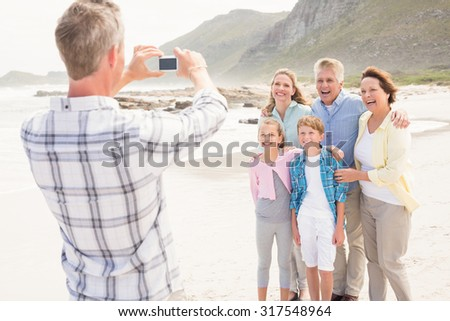Multi generation family taking a picture at the beach - stock photo