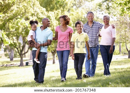 Multi-generation  family walking in park - stock photo