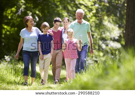 Multi Generation Family Walking Through Summer Countryside - stock photo