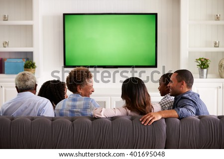 Multi generation family watching TV and laughing, back view - stock photo