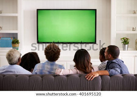 Multi generation family watching TV at home, back view - stock photo