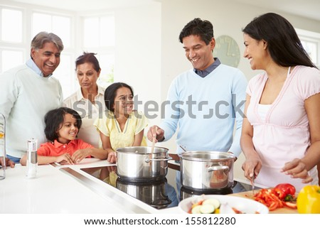 Multi Generation Indian Family Cooking Meal At Home - stock photo