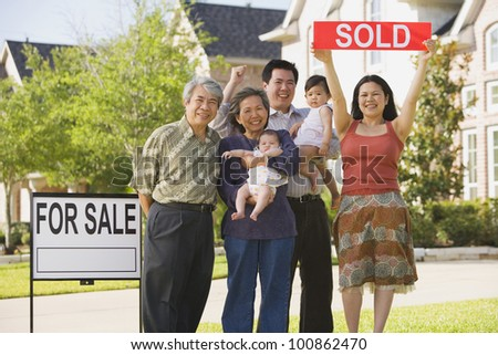 Multi-generational Asian family holding up Sold sign in front of house - stock photo