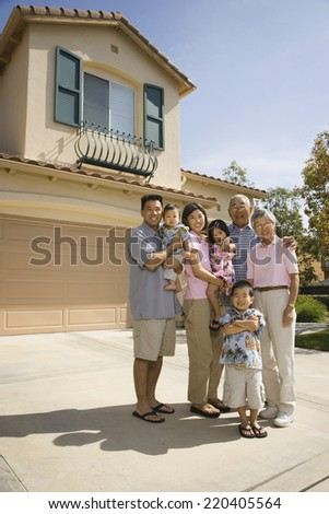 Multi-generational Asian family in driveway - stock photo