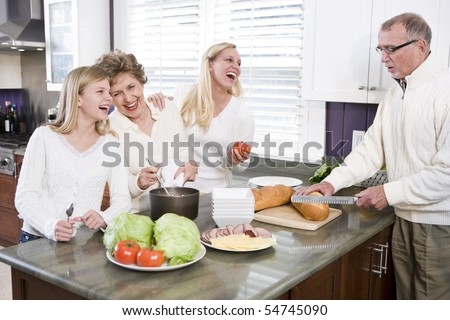 Multi-generational family making lunch in kitchen, laughing and talking