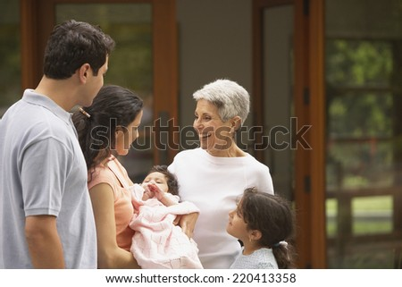 Multi-generational Hispanic family smiling at each other - stock photo