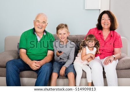 Multi Generations Family With Two Kids Watching Movie On TV Sitting On Couch Together