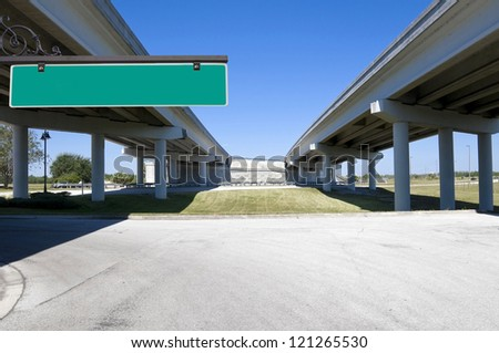 Multi-lane expressway overpass showing structural columns with blue sky with green street sign for text - stock photo