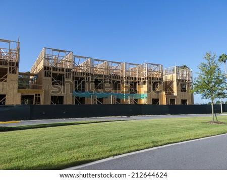 Multi level wood frame building construction with partly cloudy blue sky background - stock photo