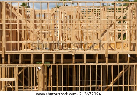 Multi level wood frame building construction with partly cloudy sky background - stock photo