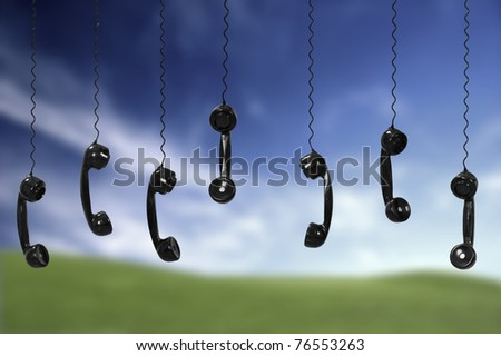 Multi old-fashioned telephones over a green meadow - stock photo