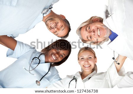 Multi racial group or happy doctors looking down smiling at the camera - Isolated on white - stock photo