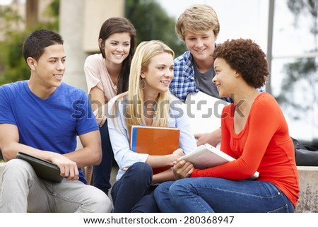 Multi racial student group sitting outdoors