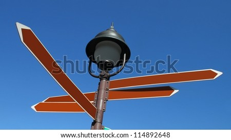 Multi street sign post with blank arrows and lantern above it - stock photo