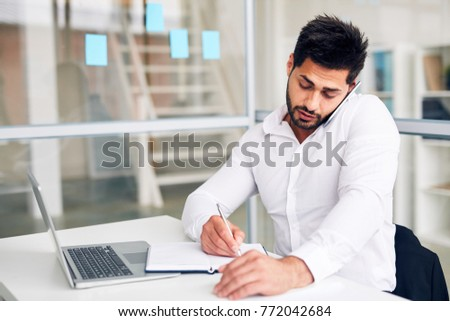 Multi-tasking office worker making notes in notebook while consulting someone by smartphone