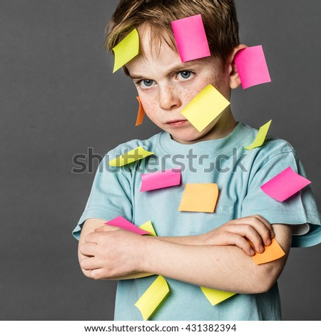 multi-tasking preschool activity - tired 6-year old kid with freckles sulking with crossed arms with copy space sticky notes all over the face to express his dislike, indoors 