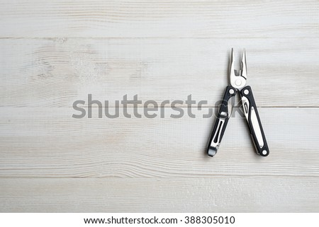 Multi tool with black handles on a white wooden background. Top view of desktop - stock photo