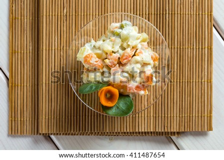 Multi vegetable salad in glass bowl on wood mat - stock photo