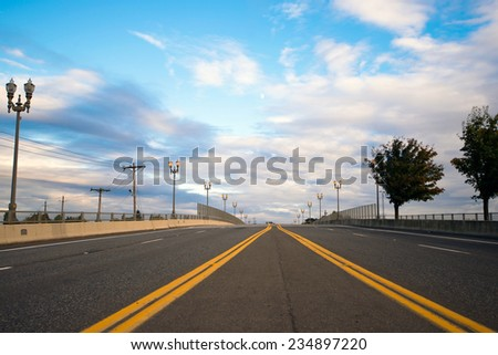 Multiband Wide asphalted road with a dividing strip oncoming traffic, marked by the yellow line, which converge on the horizon on a background of street lights and silhouette of trees along the road. - stock photo